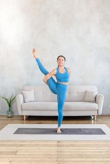 Deportes en casa mujer practicando yoga mientras está de pie en equilibrio estirando en la habitación sobre la colchoneta