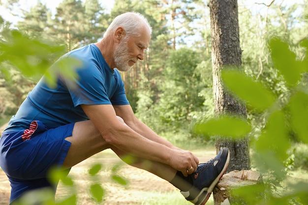 Deportes, determinación, resistencia y actividad. vista lateral del hombre mayor barbudo musculoso con estilo posando en la naturaleza salvaje, atando cordones en zapatillas de deporte, listo para correr. enfoque selectivo en el hombre