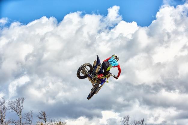 Deportes extremos, saltos en moto. el motociclista hace un salto extremo contra el cielo.