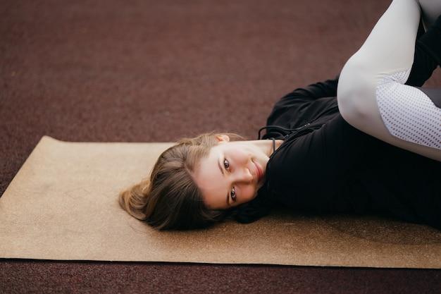 Deportes y fitness fuera del gimnasio. colocar joven mujer en ropa deportiva entrena al aire libre en el patio de recreo.