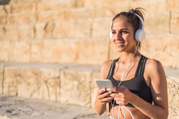 Deportes mujer descansando y escuchando música usando su teléfono móvil en las escaleras