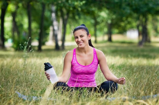 Deportes mujer tiene agua sentado en el césped en el parque