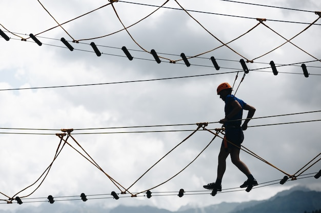 Deportes silueta masculina en un parque de cuerdas en un hermoso bosque