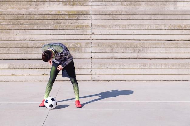 Deportista ajustando mallas junto a su pelota de fútbol