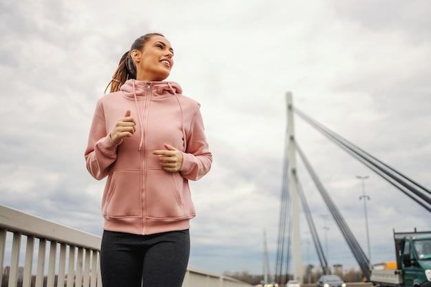 Deportista de ajuste atractivo sonriente en chándal para correr en el puente en tiempo nublado.