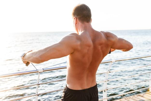 Deportista al aire libre en la playa hace ejercicios con equipamiento deportivo.