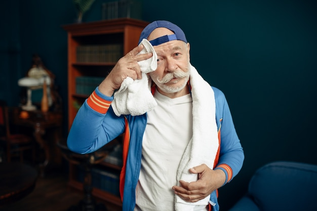Deportista anciano cansado en uniforme después del entrenamiento en casa. varón adulto en entrenamiento físico en interiores