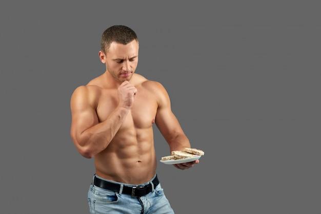 Deportista apto con el torso desnudo pensando en comer pan.