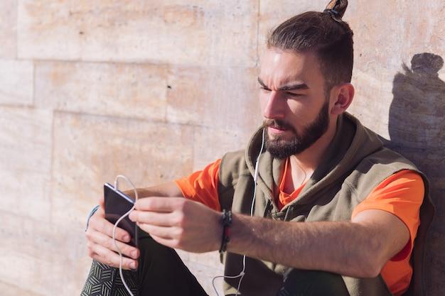 Deportista con auriculares comprobando su teléfono inteligente