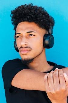 Deportista con auriculares estirando el brazo.