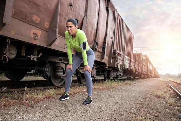 Deportista con auriculares tomando un descanso después de correr en trenes en la estación.