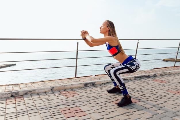 Deportista bonita haciendo sentadillas, ejercicios deportivos para el cuerpo durante el entrenamiento en el muelle