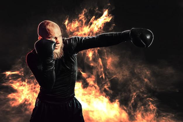 Deportista boxeador entrenando, golpeando con fuego