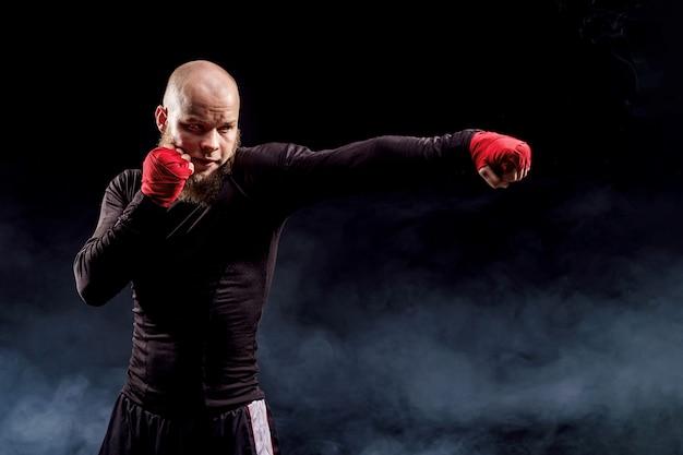 Deportista boxeador luchando en la pared negra con humo. concepto de deporte de boxeo