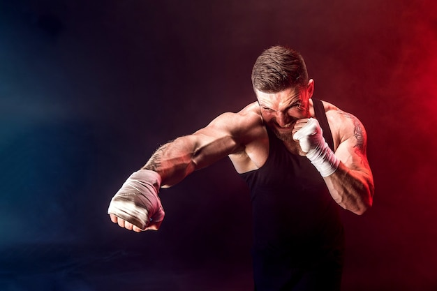 Deportista boxeador de muay thai peleando sobre fondo negro con humo.