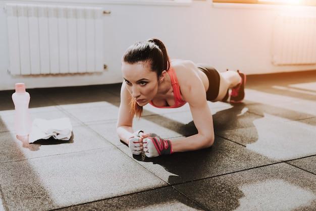 Deportista caucásica está haciendo ejercicio en el gimnasio solo