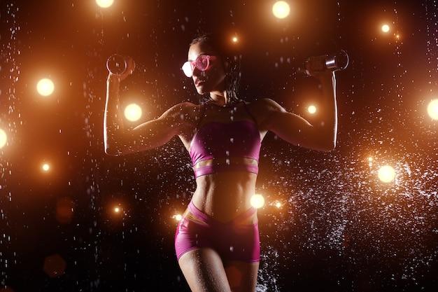 Deportista caucásica hermosa que presenta con pesas de gimnasia en un fondo negro en el espray del agua.