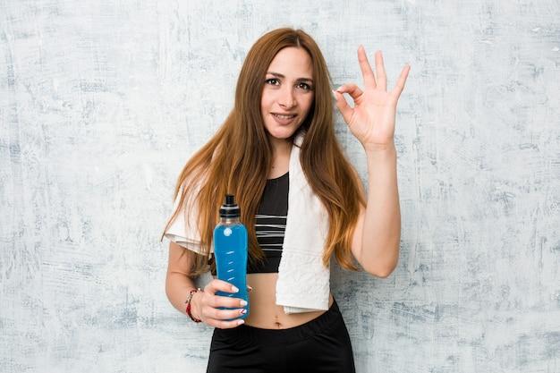 Deportista caucásica joven que sostiene una bebida isotónica alegre y confiada que muestra gesto aceptable.