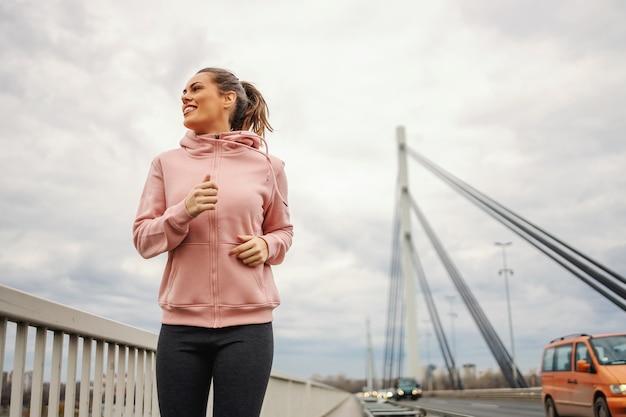 Deportista en chándal para correr en el puente en tiempo nublado. concepto de estilo de vida saludable.