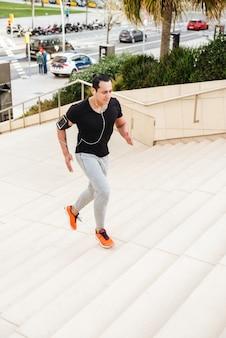 Deportista corriendo sobre pasos al aire libre en auriculares.