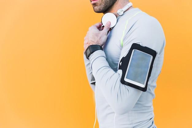 Deportista de cultivos con auriculares y teléfonos inteligentes