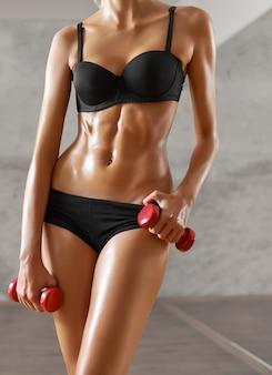 Deportista delgada, sexy, rubia, joven con cuerpo atlético, posa con mancuernas, mirando a puerta cerrada, en ropa deportiva negra, en el gimnasio. retrato de cuerpo entero.