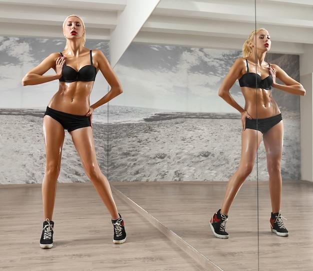 Deportista delgada, sexy, rubia, joven con cuerpo atlético, prensa bombeada, posa en el gimnasio, mirando a cámara, en ropa deportiva negra, retrato de cuerpo entero.
