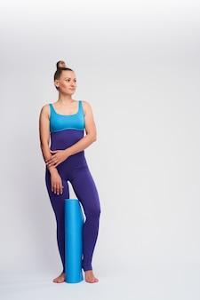 Deportista delgada sonriente en un traje de gimnasio mirando a otro lado mientras sostiene la estera de fitness