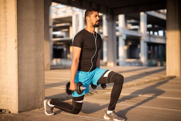 Deportista escuchando música y entrenando con pesas.