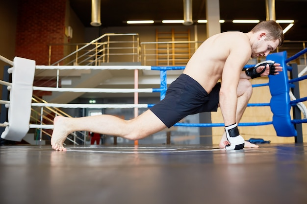 Deportista estirando las piernas en el ring de boxeo