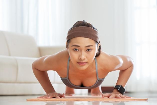 Deportista étnica entrenando en colchoneta
