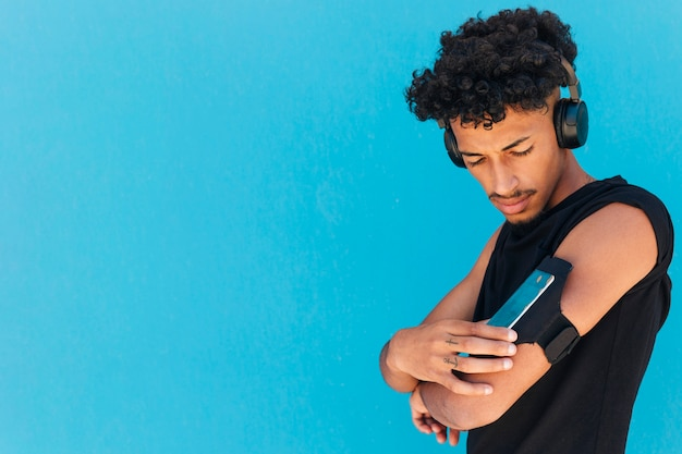 Deportista étnico con auriculares utilizando teléfono en brazalete.