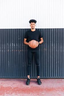 Deportista étnico con balón de baloncesto.