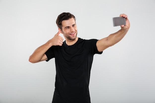 Deportista feliz hacer selfie por teléfono móvil.