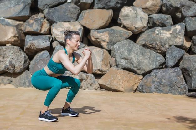 Deportista fuerte en cuclillas cerca de la pared de piedra