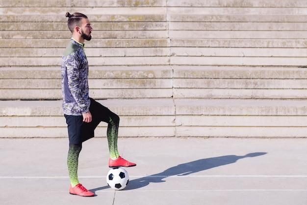 Deportista guapo en una cancha de fútbol de hormigón