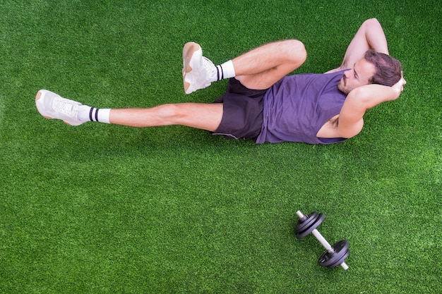Deportista guapo durante sus flexiones de entrenamiento al aire libre