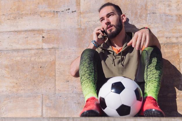 Deportista hablando por teléfono descansando con su bola