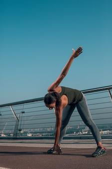 Deportista haciendo calentamiento al aire libre en el puente y tocando el suelo
