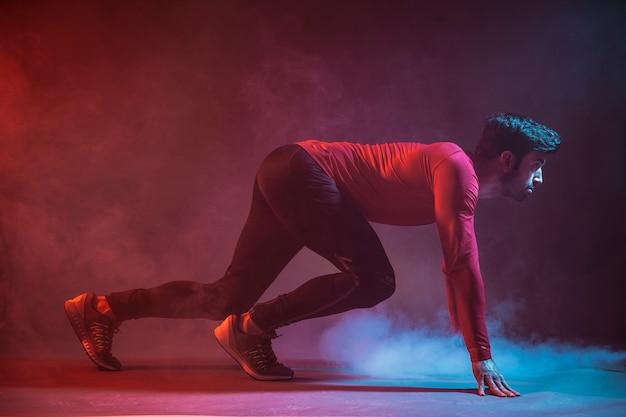 Deportista haciendo crouch start en la oscuridad