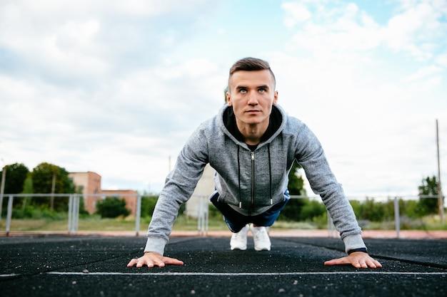 Deportista haciendo ejercicios de flexiones de brazos, trabajando en frente en el estadio