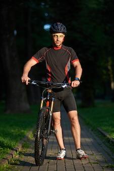Deportista hombre sonriente ciclista caminando cerca de bicicleta feliz de comenzar la mañana con el entrenamiento.