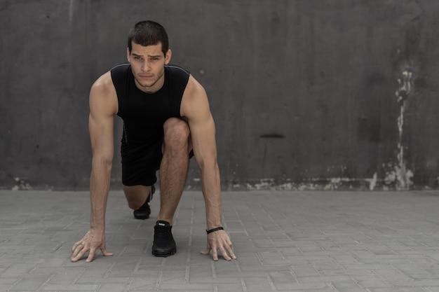Deportista iniciando su sprint en una pared industrial gris