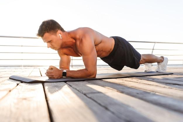 Deportista joven guapo hacer ejercicios en la alfombra de deporte escuchando música.