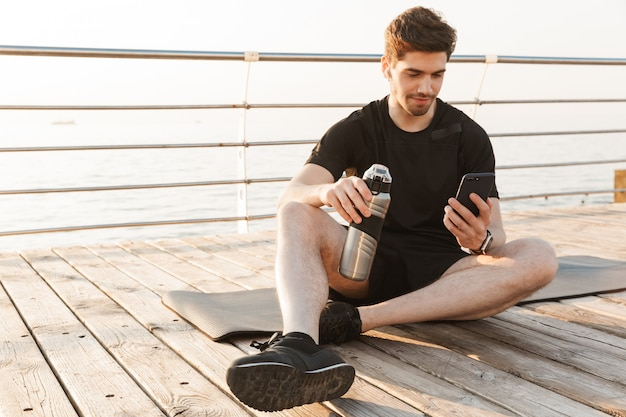 Deportista joven guapo sentado al aire libre escuchando música