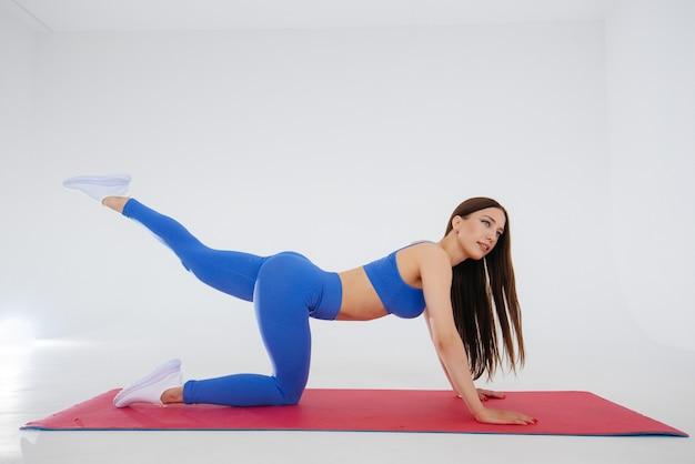 Deportista joven sexy realiza ejercicios deportivos en una pared blanca