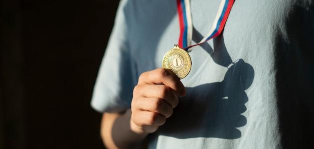 Un deportista masculino con una medalla de oro en el pecho, líder campeón