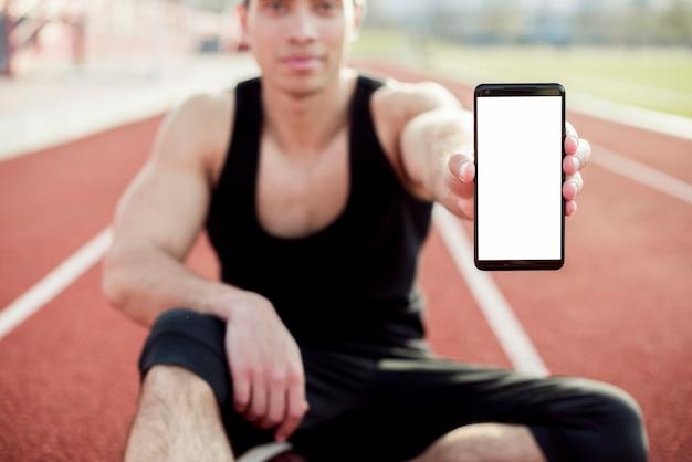 Deportista masculino sentado en la pista de carreras mostrando la pantalla del teléfono móvil