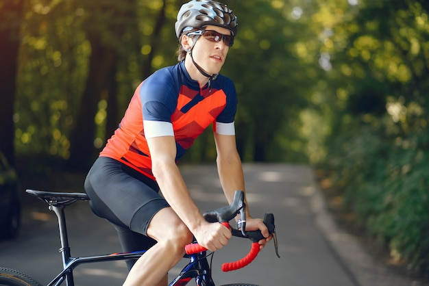 Deportista montando bicicleta en el bosque de verano