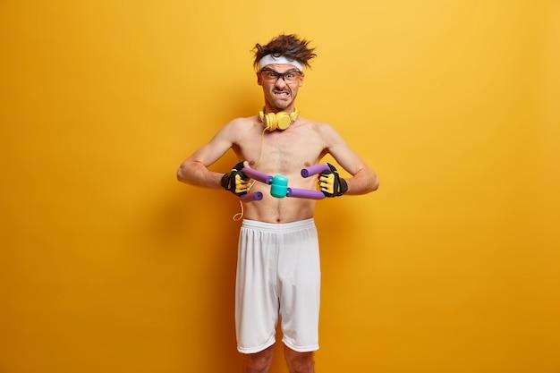 Deportista motivado cansado del esfuerzo físico agarra el expansor con fuerza, aprieta los dientes, entrena los músculos, usa pantalones cortos blancos, calienta el cuerpo, se estira solo tiene un cuerpo delgado aislado en una pared amarilla